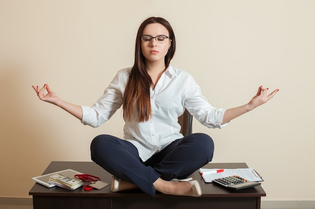 Accountant sitting in yoga pose on the table