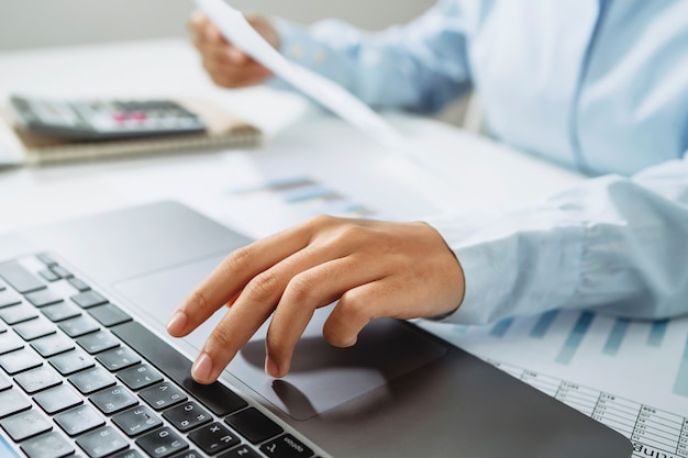 Accountant use calculator and computer with holding pen on desk in office. finance and accounting concept