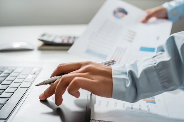 会計士は、オフィスの机の上にペンを持ってラップトップコンピューターを使用します。財務および会計の概念