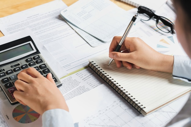 Accountant using calculator for calculate budget finance on table in office