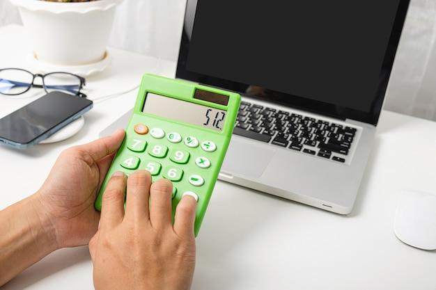 Бухгалтер работает и анализирует финансовые расчеты с помощью калькулятора и портативного компьютера