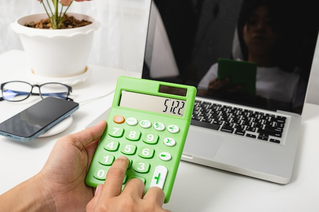 회계사는 계산기와 노트북 컴퓨터로 재무 계산 작업 및 분석