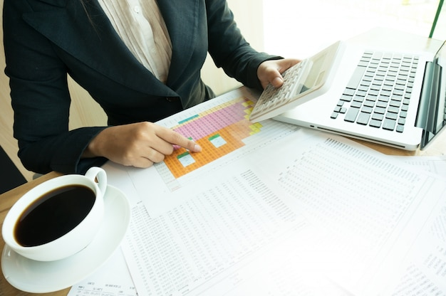 Accountant working women uses calculator with spreadsheet document, information financial concept.