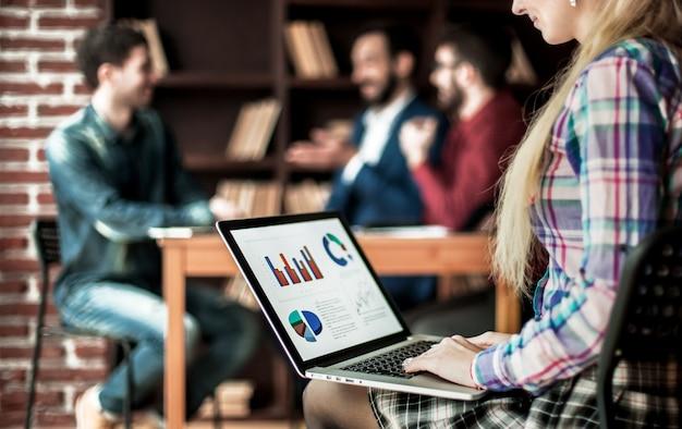 Бухгалтер работает с финансовыми графиками на ноутбуке в офисе