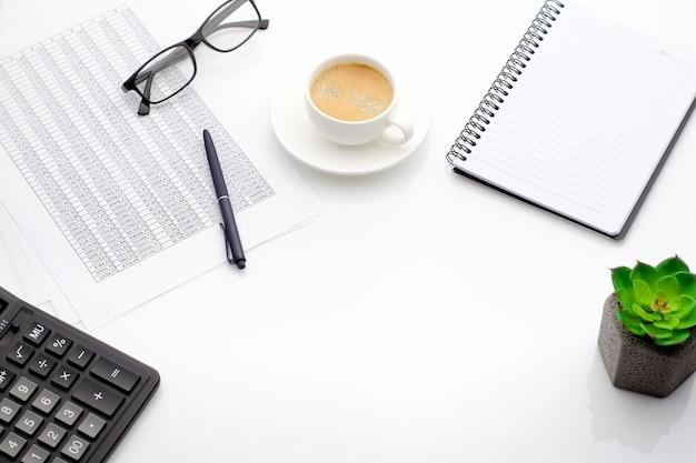 会計ビジネスの概念。一杯のコーヒー、電卓、グラス、メモ帳、スプレッドシートを備えたデスクトップ。スペース構成をコピーします。セレクティブフォーカス