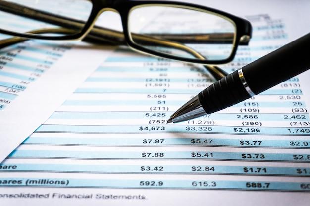 会計のビジネスコンセプトです。会計報告と財務諸表を机の上に置いた眼鏡