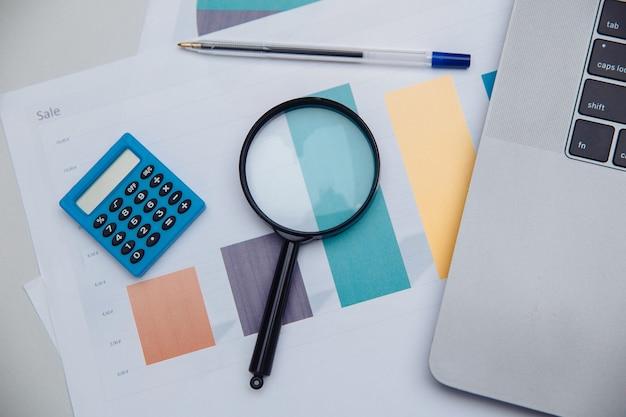 Калькулятор бухгалтерского учета, диаграммы и увеличительное стекло. концепция бизнеса и финансов