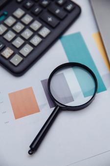 Калькулятор бухгалтерского учета, диаграммы и увеличительное стекло