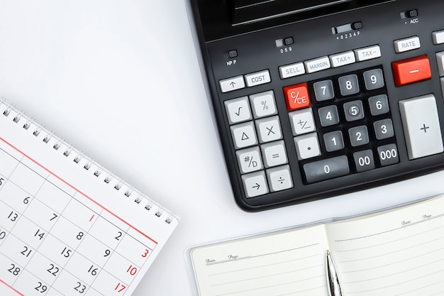 Accounting calculator with tax button, notepad, silver pan, table calendar. tax time payment deadline business concept. copy space.