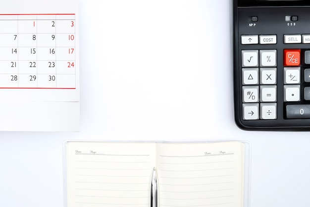 Accounting calculator with tax button, notepad, silver pan, table calendar on white background. tax time payment deadline business concept. copy space.
