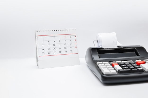 Accounting calculator with tax button and table calendar tax time payment deadline business concept. copy space.