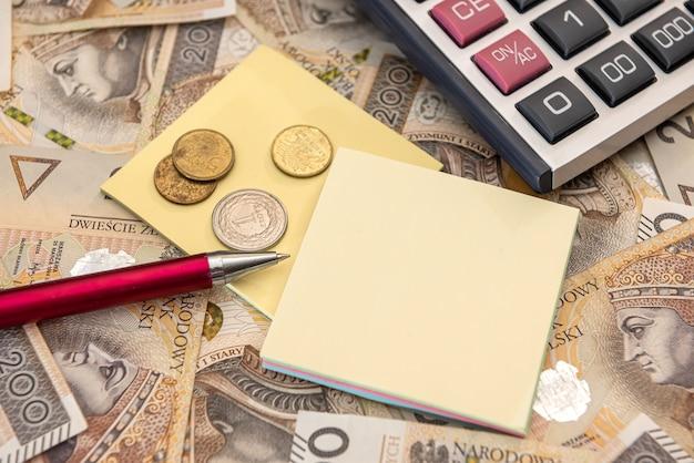 회계 개념 - 계산기 펜과 메모가 있는 폴란드 즐로티 지폐