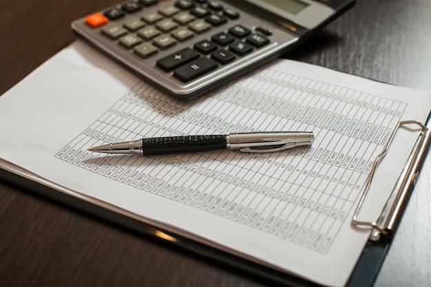 Отчетные документы, ручки и калькулятор крупным планом