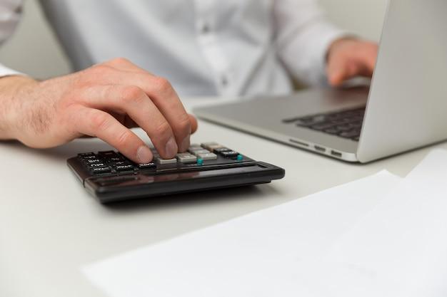 オフィスでの会計。ノートパソコンと電卓の操作