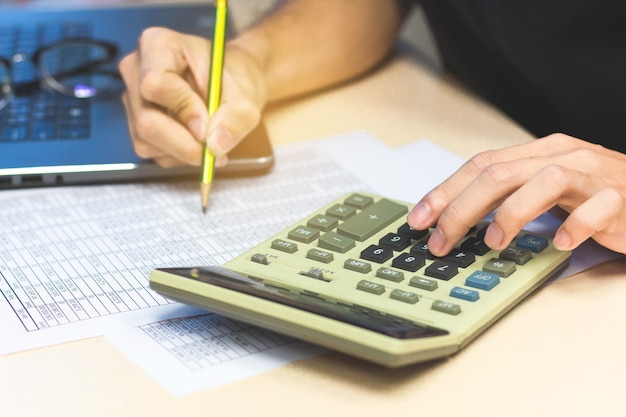 Accounting man hands  pressing calculator buttons and holding pencil checking documents