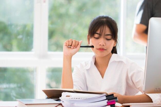 会計計画予算レポートファイルの概念:アジアのビジネスウーマンオフィスは、コンピューターの忙しいオフィスでドキュメントペーパーの未完成のスタックのドキュメントの作業をチェックします。事務処理を探すためのアイデア。
