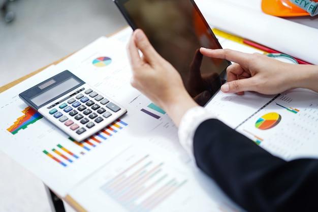 Таблетка прессы бухгалтерии с калькулятором и диаграмма для работы в офисе.