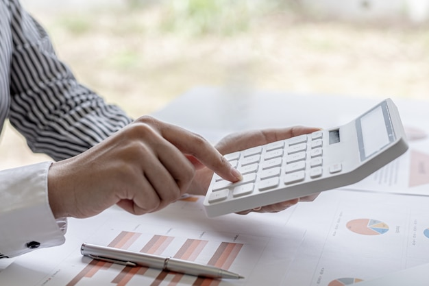 An accounting scholar is pressing a calculator, she is calculating the numbers shown on the company's income statement and financial documents, she is a company auditor. audit concept.