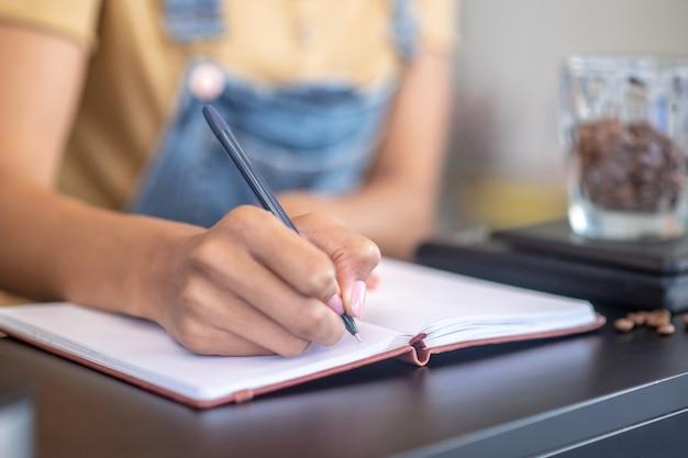 Бухгалтерский учет. женский тонкий изящный почерк с ручкой в блокноте вес кофейных зерен на прилавке