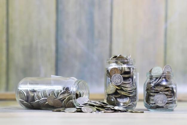 Накопленные монеты в стеклянных банках на полу