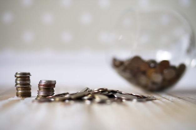 Accumulated coins stacked in piles on the wooden floor