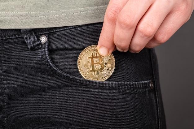 Накопление биткойнов, золотая монета btc в кармане крупным планом.