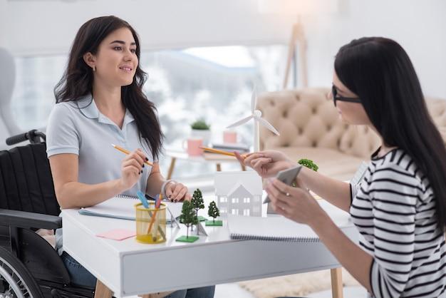 正確なモデリング。創造的な障害のある女性と同僚が鉛筆を使用しながらソーラーパネルについてチャット