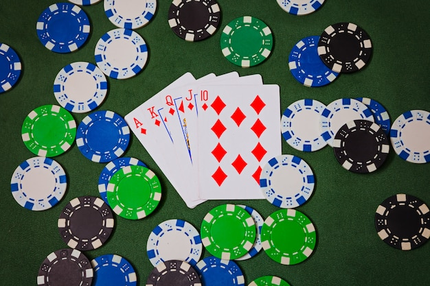 에이스, 킹, 퀸, 잭, 텐, 다이아몬드가 포커 칩에 놓여 있습니다.