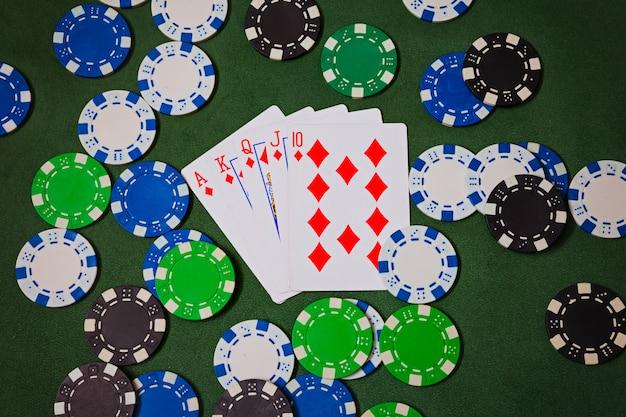 Ace, king, queen, jack, ten, diamonds lie on poker chips