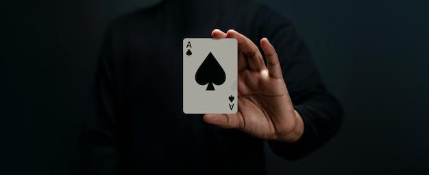 Игральная карта ace spade. игрок или фокусник с покерной картой. передний план. крупный план и темный тон