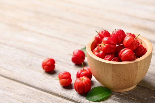 Acerola cherry in wooden bowl on wooden table.