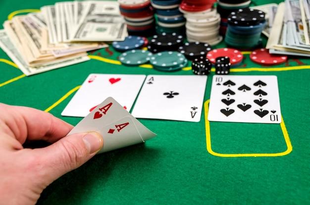 ポーカーテーブルのプレーヤーの手にあるエース