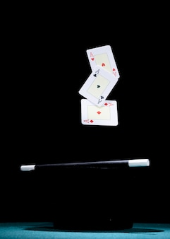 Aces plying card over the black top hat and magic wand against black background