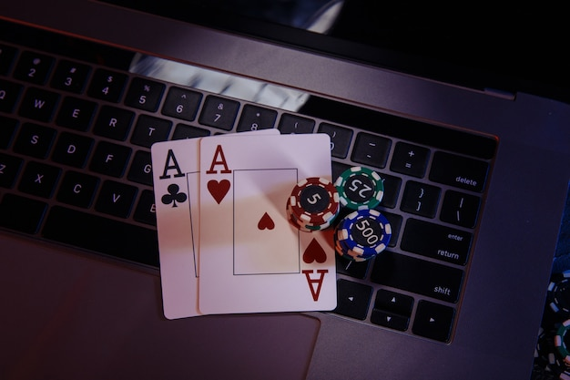 Aces with playing chips on a laptop's keyboard.