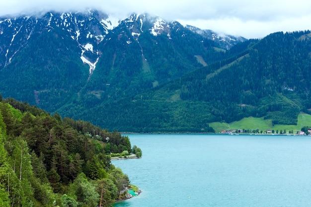 Летний пейзаж ахензее (ахенского озера) с облачным небом и снегом на вершине горы (австрия).