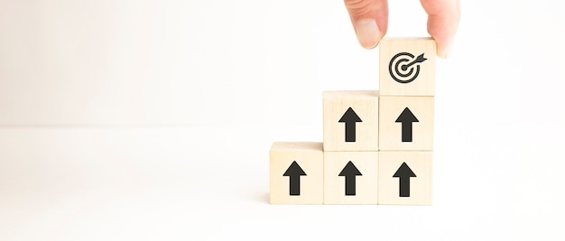 Achievement business target concept , businessman holding and stacking wooden cubes block which print
