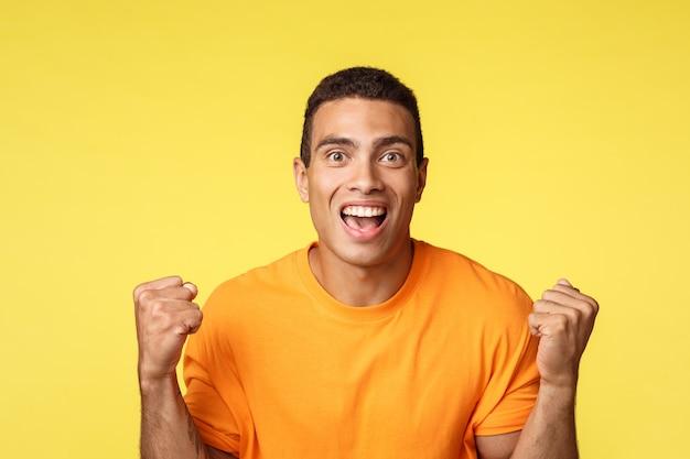 Концепция достижения, празднования и выиграть. красивый облегченный веселый молодой человек сжимает руки, кулак насос и улыбается стать победителем или чемпионом, получить приз, добиться успеха, желтый фон
