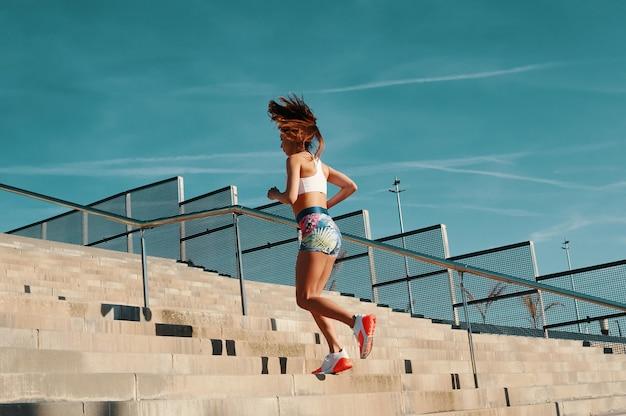 最良の結果を達成する。屋外で運動しながら走っているスポーツウェアの美しい若い女性の全長