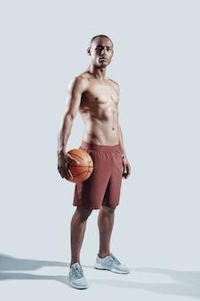 最良の結果を達成する。灰色の背景に立っている間カメラを見ているスポーツ服のハンサムな若いアフリカ人の完全な長さ