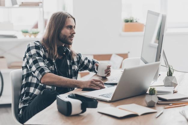 最良の結果を達成する。コンピューターで作業し、創造的なオフィスで彼の机に座っている間コーヒーを保持している長い髪のハンサムな若い男
