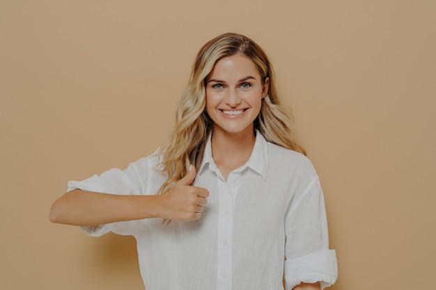 目標の達成。ベージュの壁に対してスタジオでポーズをとって、幸せな表情でカメラを見て、手で親指を立てるジェスチャーを示す広い笑顔でポジティブな若い女性の肖像画。ボディランゲージ