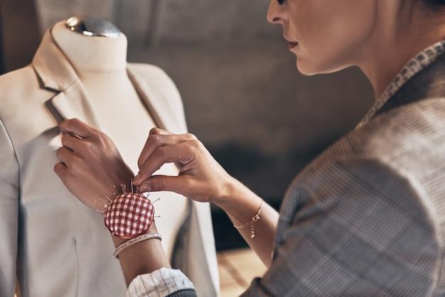 Достичь успеха как дизайнер. крупным планом вид сзади молодой женщины, использующей швейные иглы, стоя в своей мастерской