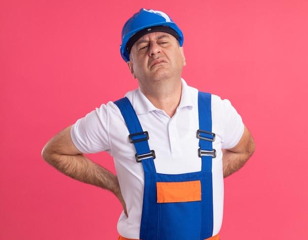 L'uomo adulto dolorante del costruttore in uniforme trattiene isolato sulla parete rosa