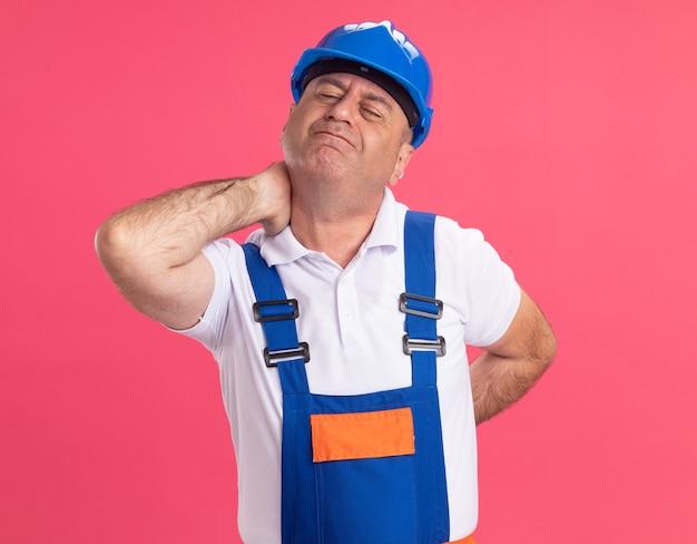 L'uomo caucasico adulto doloroso del costruttore in uniforme tiene il collo e la schiena sul rosa