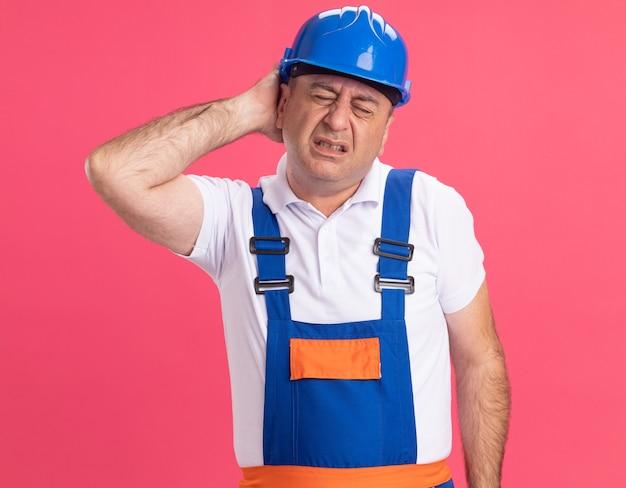 L'uomo caucasico adulto doloroso del costruttore in uniforme mette la mano sulla testa isolata