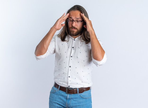 Un bell'uomo adulto dolorante con gli occhiali che tiene le mani sulla testa con gli occhi chiusi isolati sul muro bianco
