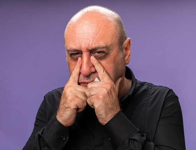 Больной взрослый больной кавказский мужчина кладет пальцы на веки, изолированные на фиолетовой стене с копией пространства