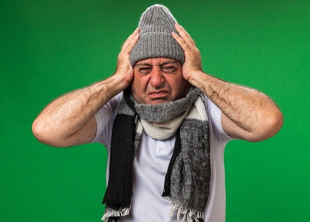 Adulto dolorante malato uomo caucasico con sciarpa intorno al collo indossando cappello invernale tenendo la testa isolata sulla parete verde con spazio di copia
