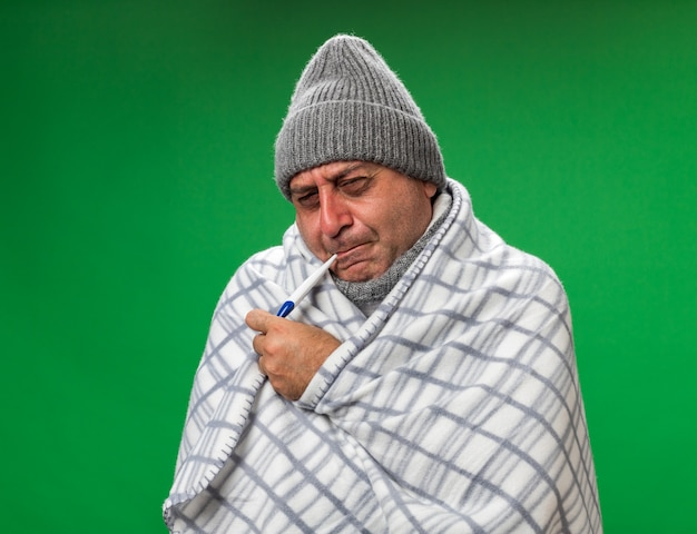 Aching adult ill caucasian man with scarf around neck wearing winter hat wrapped in plaid holding thermometer in his mouth isolated on green wall with copy space