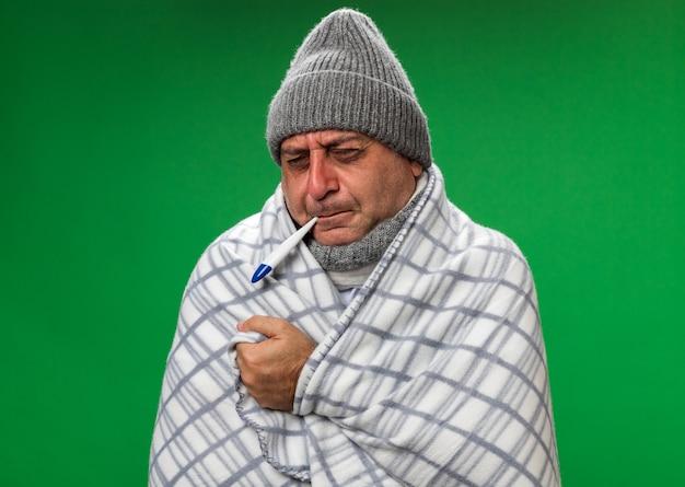 Uomo caucasico malato adulto dolorante con sciarpa intorno al collo che indossa cappello invernale avvolto in supporti a quadri con gli occhi chiusi tenendo il termometro in bocca isolato sul muro verde con spazio di copia